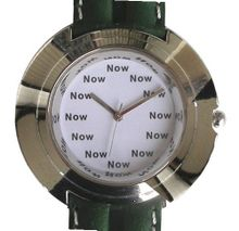 """Now"" Is the Time That Is Shown Each Hour on the White Dial of the Jumbo Size Polished Chrome Round with a Green Leather Strap with White Stitching"